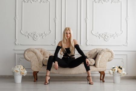 Sexy schöne junge Modellfrau in modischer schwarzer Kleidung mit Jeans sitzt auf einem Sofa in einem Vintage-Zimmer