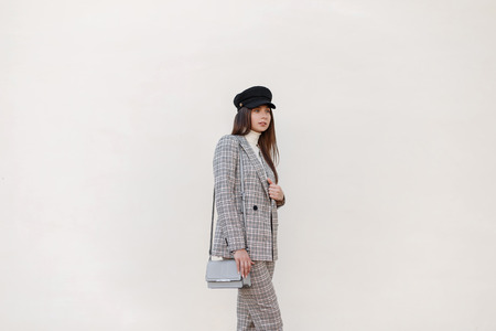 Stylish beautiful young woman with a hat in a fashionable checkered suit with a handbag on the street near the wall