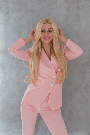Fashion attractive young woman with blond hair smiling in long pink suit posing near a gray wall