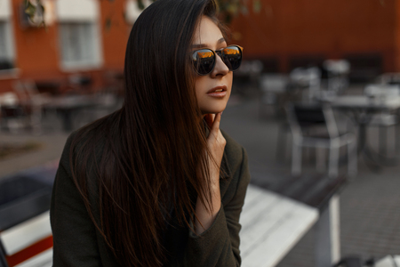 Portrait of a stylish and young brunette girl wearing a green coat and sunglasses, sitting outdoors against a background of a street cafe. Outdoor lifestyle. Fashionable woman. 스톡 콘텐츠 - 111784475