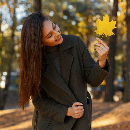 Happy young beautiful woman with a smile in a fashionable coat with a yellow autumn leaf walks in the park on a sunny day Stock Photo
