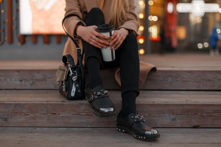 Young blonde girl in an autumn warm coat with stylish black jeans, in black leather vintage fashionable modern shoes and with a fashionable bag sits on the stairs with a cup of coffee.Women's clothing Archivio Fotografico