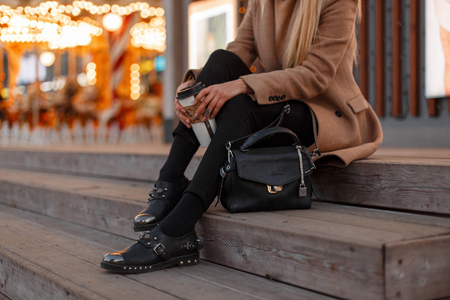 Young girl in a vintage coat with a warm knitted sweater, stylish jeans, black leather fashionable modern shoes and a stylish leather bag sits with a cup of coffee. Women's stylish clothing. Close-up Archivio Fotografico