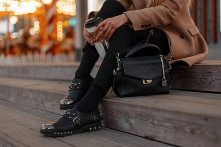 Young hipster girl in an autumn vintage coat with stylish black jeans, in black leather fashionable modern shoes and with a small bag sits on the stairs with a cup of coffee. Women's legs with shoes