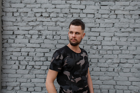 Attractive brutal young man in a fashionable camouflage military T-shirt, with a hairstyle and stylish beard stands on the street near a gray brick wall. Stylish guy.