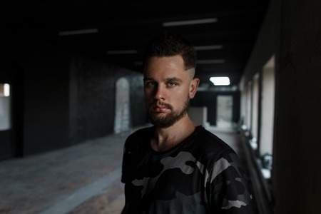 Attractive young man with a stylish hairstyle and beard, wearing a modern camouflage green T-shirt stands and in a dark studio near a white wall and looks into the camera. Brutal guy Stock Photo