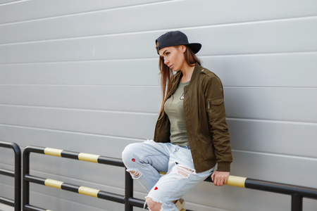 Beautiful young stylish woman in a black stylish baseball cap in a fashionable green jacket in a green T-shirt with torn blue jeans sits against a silver wall. Fashionable girl. Street fashion Stock Photo