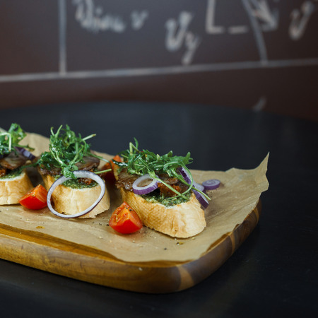 White bread sandwiches with meat pate with red onion rings with arugula and slices of red fresh tomatoes on a wooden board in a restaurant. Delicious food and healthy dinner Banco de Imagens