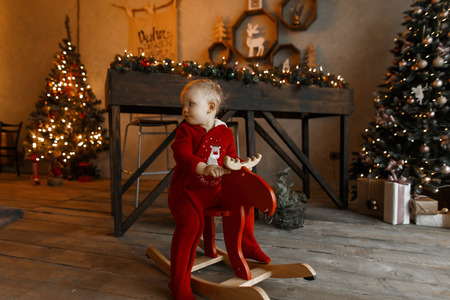 Little cute child in a red Christmas plush fashionable costume sits and swinging on the rocking wooden red deer chair in a room decorated with Christmas garlands and lights. Magic moment Archivio Fotografico