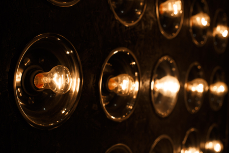 Electric bright gold vintage incandescent bulbs on a black background. Modern spotlights as an interior item. Close-up