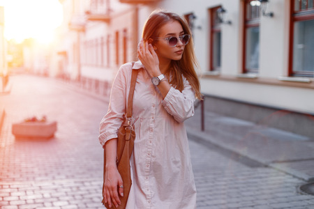 Fashionable young hipster woman in stylish sunglasses in trendy white dress with a fashionable brown leather bag in a city stand on the background of the sun's rays. Attractive stylish girl. 写真素材 - 115295336