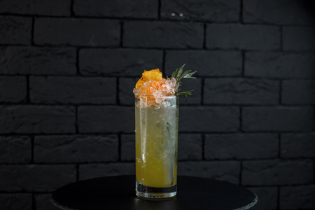 Pineapple light alcoholic cocktail in a  glass with vodka with white rum with coconut syrup with pieces of ice decorated with yellow fruit. Choice of modern gourmet Stock Photo