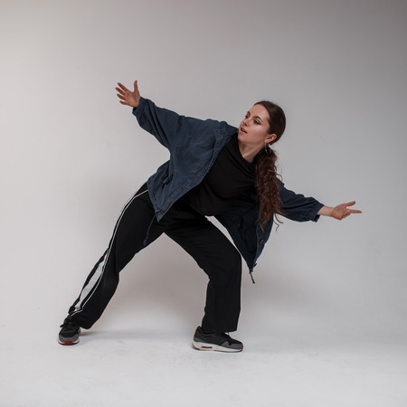 Attractive young beautiful woman dancer in a stylish blue shirt in a T-shirt in black sweatpants learns the dance moves in a bright studio. Lovely hipster girl