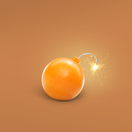 Concept orange bombs on yellow background. Creative bomb with sparks. Juicy Orange