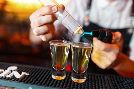 Bartender man making hot alcohol shots on the bar in the pub with a professional burner. The bartender lights a lighter over a glass.Relax in the nightclub. Hot fire drinks. Lets the party