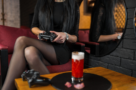 Young woman in a black dress sits in a bar with cocktail holding a black joystick in her hands and playing a modern video game. Gambling girl gamer. Interesting party. 版權商用圖片