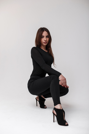 Cute young woman in a stylish T-shirt in stylish black leggings and leather stylish shoes with heels posing sit in the studio near the white wall. Fashionable sexy girl 免版税图像