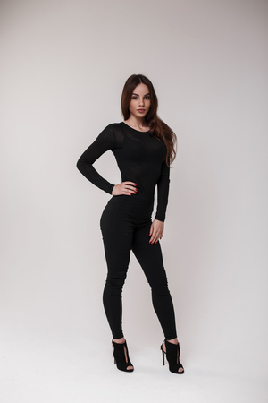 Sexy attractive beautiful brown-haired woman in a black stylish T-shirt in stylish black leggings and leather sandals on his heels is standing and posing in a bright room on a white background. Girl