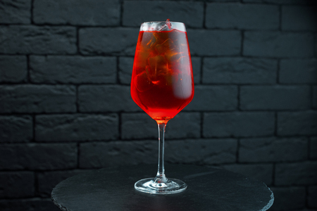 An unusual sweet tasty red cocktail in a glass glass with vodka with natural juice with the addition of pomegranate syrup and white rum is on the table in the bar. The drink is served chilled. Stock Photo