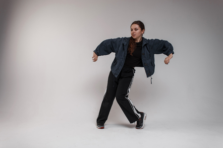 Stylish young pretty woman dancer in a denim jacket in a shirt in fashionable black pants is dancing hip-hop in the studio near a white wall. Modern choreography. Talented girl