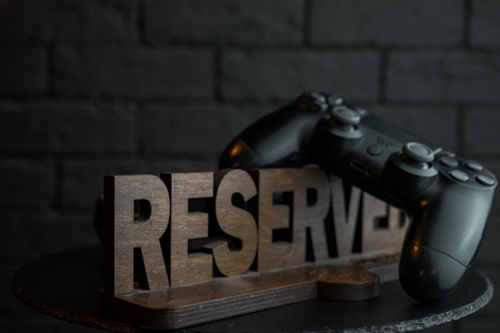 Vintage wooden exclusive figure Reserved next to the joystick for playing in the video games on an wooden black table against a black brick wall. Places for VIP guests. Great weekend. Stock Photo