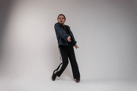 Charming young woman dancer in a denim blue shirt in a black t-shirt in black sweatpants in sneakers dancing modern dance in a room on a white background. Cute girl