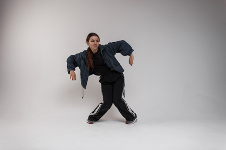 Pretty young female dancer in a denim jacket in a black stylish T-shirt in sweatpants is dancing in a bright studio near a white wall. Athletic stylish girl. Modern dance
