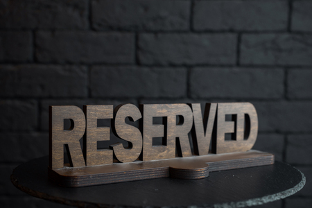 Vintage wooden carved figure Reserved on an empty black table in a restaurant against a black brick wall. Exclusive decorative plate Reserved. Table for VIP guests.