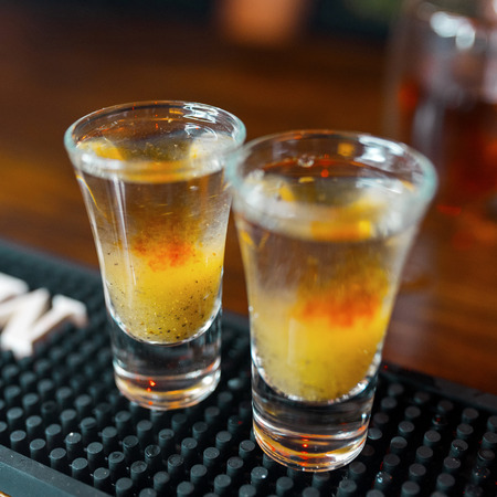 Two alcoholic sweet double-layer shots with vodka and fruit syrup stand in the club at the bar. Weekend at the bar. Night club life. Close-up