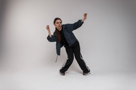 Charming young cute woman dancer in blue jacket in stylish t-shirt in black sport pants dancing hip-hop in classroom