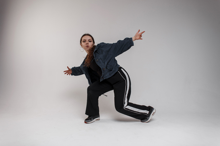 A young beautiful woman dancer in a stylish denim shirt in a T-shirt in black sweatpants in black sneakers demonstrates dance moves in a bright studio. Cute girl