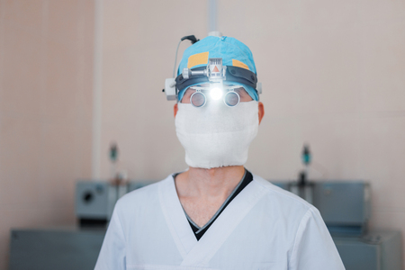 young neurosurgeon man in glasses with binary loupes for microsurgery with light in the operating room. Modern medicine. Imagens