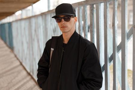 Junger attraktiver ernster Hipster-Typ in schwarzer Sonnenbrille in einer stylischen schwarzen Jacke in einer schwarzen Mütze nahe dem Hintergrund eines Holzzauns. Stilvoller Amerikaner. Standard-Bild