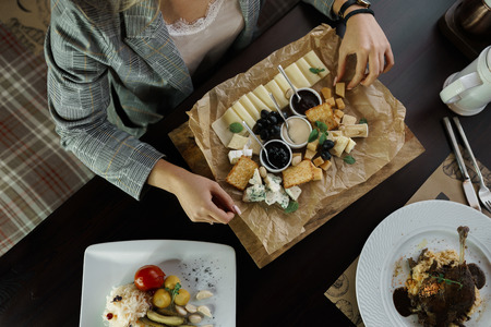 Business woman sitting at a table in a restaurant and is holding in hand a plate of cheese on the background of other dishes. Easy tasty snack. Useful lunch in a cafe. Top view of the table with food. 版權商用圖片 - 115368896