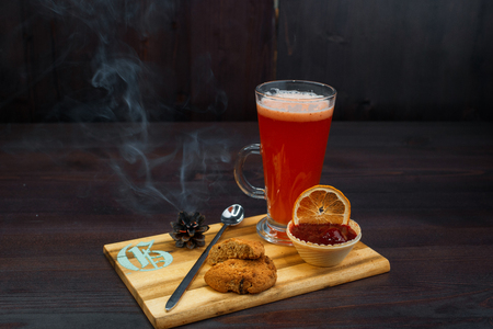 Tasty sweet hot red flavored tea with strawberry jam and oatmeal cookies stands on a wooden vintage table in a cafe. Sweet warm warming drink. Cozy atmosphere.