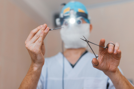 Man surgeon in a medical mask wearing glasses with binocular loupes is standing in the operating room and holding surgical scissors. Operation process Фото со стока