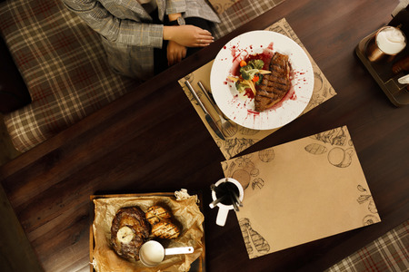 A woman sits at a wooden table in a restaurant and eats a delicious juicy beef steak Striploin with baked broccoli and carrots in a wine sauce. Delicious healthy dinner. Top view Stok Fotoğraf