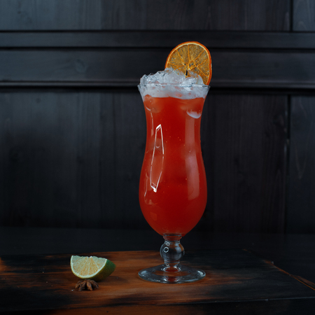 Delicious alcoholic cocktail in a glass with vodka and white rum with the addition of natural cranberry juice with fresh orange and lime slices on a table in a nightclub against a dark background.