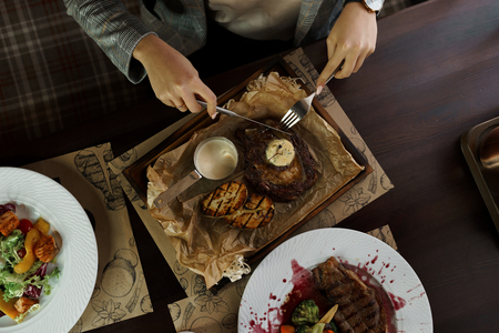 Business woman eating beef steak with butter on wooden table in a restaurant. Time for healthy lunch. Top view