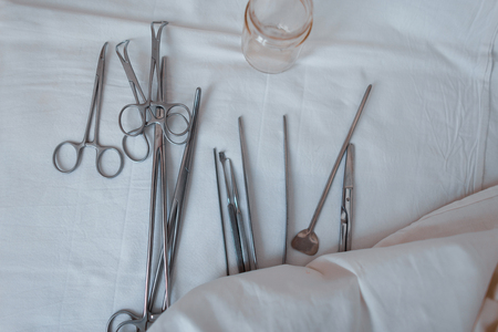 Surgical instruments made of steel including scalpels, forceps and tweezers, located on a white table. Medical equipment. Close-up