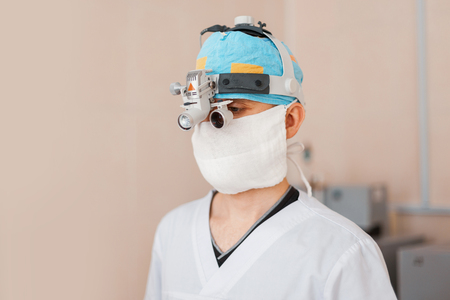 surgeon man in a mask in special medical clothes wearing glasses with a binocular magnifying loupes is standing in the operating room. Modern medicine.