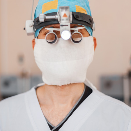 Young neurosurgeon man in a medical mask with professional magnifying glasses with binary loupes for microsurgery. Instruments for surgery