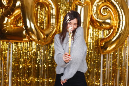 Happy smiling young woman in gray vintage knitted sweater celebrates New Year with fireworks against the background of golden balloons 2019 in the studio. Positive girl at the New Year party. Standard-Bild