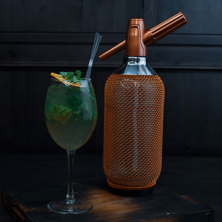 Beautiful alcoholic cocktail in an elegant glass with the addition of tequila and fresh mint leaves stands on a vintage table in a restaurant near the golden luxury bottle. Exotic drink Reklamní fotografie