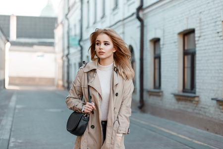 Stylish young woman in a spring light coat in a white T-shirt with a stylish black leather handbag walking down the street against the backdrop of an old brick building. Fashionable cute European girl