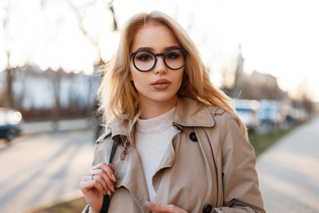 Portrait of amazing cute young hipster woman with beautiful lips in stylish glasses in a spring stylish coat in a white T-shirt on the street in the spring afternoon. Attractive fashionable girl. Banco de Imagens