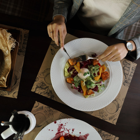 View over hands with cutlery and vegetable salad and poached egg on a white plate indoors on the table. Fork and knife in the hands of the woman. Healthy breakfast Stock Photo