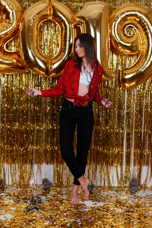 One young happy woman dances and smiles against the background of golden garlands and balloons 2019. The girl is glad to the New Year. Merry Christmas to you. Stock Photo - 115370726