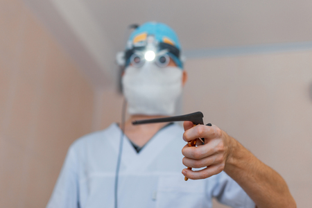 Microsurgeon man in a medical mask in a white robe in binocular loupes stands in the operating room and holds a surgical clip in his hand. Neurosurgery Instruments. Operation process