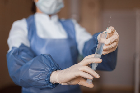 Doctor in medical gloves hold a syringe with an antibiotic. A nurse prepares to give an injection. Close-up